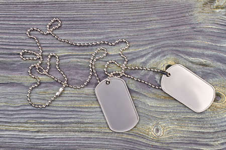 3c0e1f9be5f9 Military Dog Tag close up. Dog tag with a chain on grey wood background