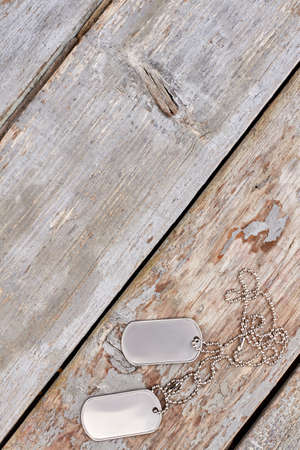 Dog tags on wood and copyspace. Silver army necklace.