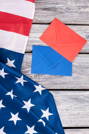 American flag and two colored envelopes. USA patriotic flag and envelopes on old wooden background.