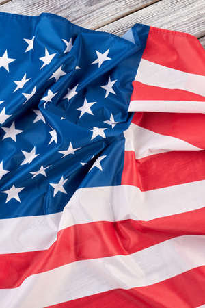 American national flag, top view. Crumpled flag of USA on wooden background.