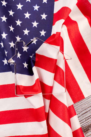 Flag of USA and metal house shaped form. House pastry cutter shape and USA flag background, vertical image. Stock Photo