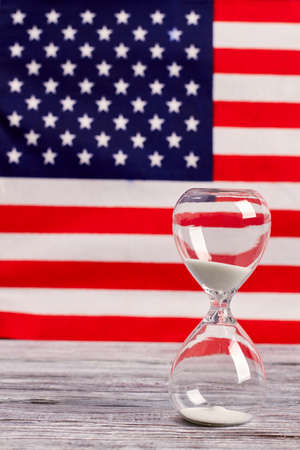 Sand glass on wood with American flag in the background. Sand clock on wooden table with national flag of USA in the background, vertical image.