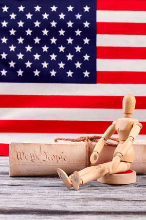 Constitution of US and wooden human dummy. Wooden figurine sitting at the constitutional document of USA with American flag in the background.