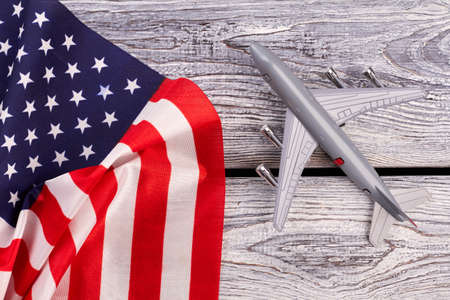 Plastic toy jet plane and flag of USA. American flag and grey toy air plane on wood close up. Flight to USA.