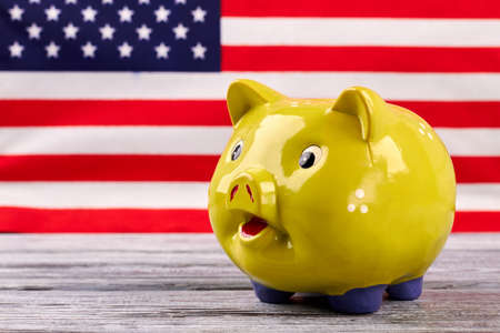 Money box on USA flag background. Yellow piggy bank on old wooden table with blurred American flag in the background. Financial and economics concept. Stock fotó