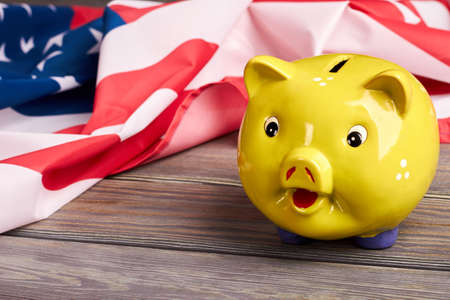 Close up yellow piggy bank and USA flag. American national flag and money box on wooden background. Budget and savings.