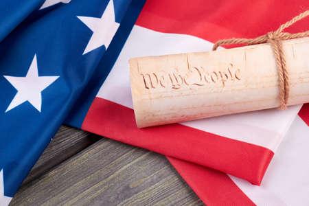 Gros plan drapeau américain et document. Document enroulé et drapeau américain sur fond en bois se bouchent. Constitution des États-Unis.