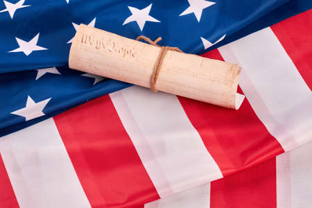 US Constitution on national flag of USA. United States constitution with american flag. Declaration of Independence of the USA. Stock Photo