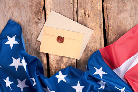 Craft envelopes and USA flag. Stars and stripes flag with brown envelopes on rustic wooden planks.