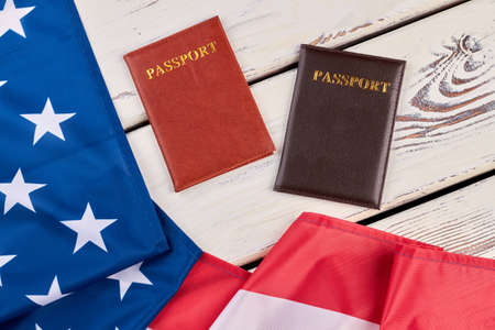 American flag and passports on wood. USA flag and two passports on white wooden background close up, horizontal image.
