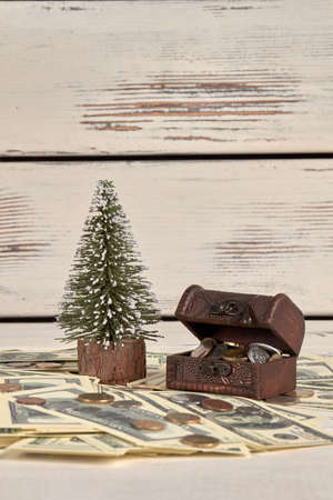 Pile of money, moneybox chest and christmas tree. Dollars and coins. White wood background.