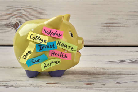 Yellow pig moneybox. White wood background.
