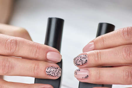 Female nails trendy art design. Womans hands with varnished nails holding bottles of nail polish. Beauty salon and spa. Banque d'images