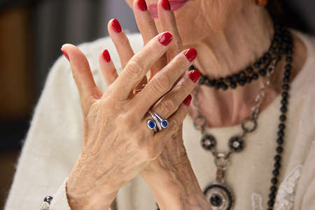 Old womans manicured hands with ring. Hands of senior woman painted with red nails close up. Concept of female treatment and wellness. Stock Photo