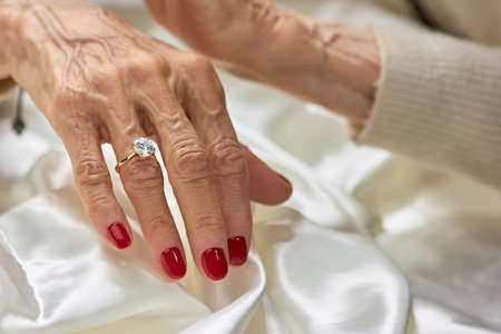 Female aged hand with diamond. Senior woman hand with red manicure wearing golden ring with diamond. Stock Photo