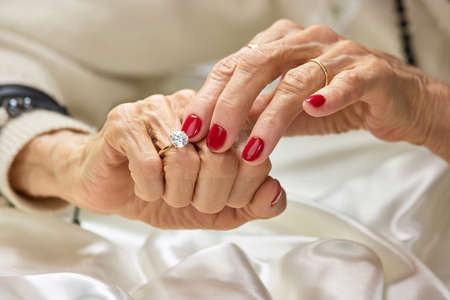 Old woman touching the diamond on her finger. Senior woman hands with beautiful red manicure wearing ring with a diamond. Womens precious jewels on hand. Stock Photo