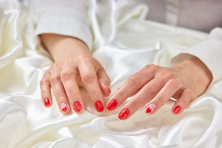Female red manicure and white silk. Young woman hands with red heart pattern nails on white silk fabric. Concept of woomanhood and delicacy. Stock Photo