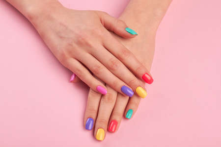 Female hands with colorful polish nails. Woman well-groomed hands with multicolor nails on salon table. Manicure nail painting. Banque d'images
