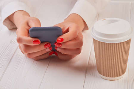Female hands with smartphone and coffee. Woman manicured hands holding touch screen phone next to cardboard disposable cup with cappuccino.