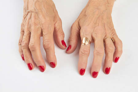Manicure with red nails on white background. Close up of hands of old woman with short red manicure on nails isolated on white background. Beautiful red manicure on female hands.