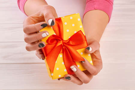 Woman hands holding present box. Well-groomed female hands holding yellow gift box with red bow. Trendy matte manicure.