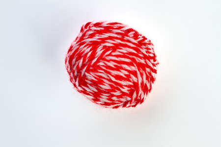 Ball of red yarn on white background. Ball of red and white yarn for knitting isolated on white background.