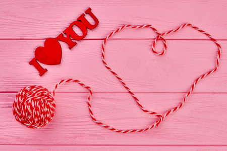 Valentines Day background with heart from threads. Red wooden inscription I love you. Red ball of yarn. Happy Valentines Day.