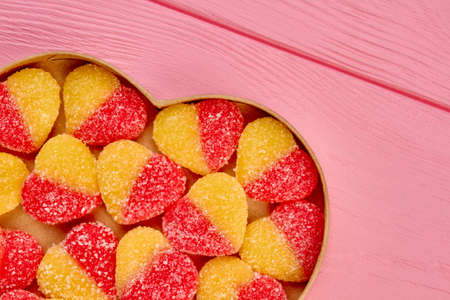 Valentines Day background with candies coated with sugar. Heart shaped sweets covered with sugar crystals in heart shaped box, top view. Stok Fotoğraf
