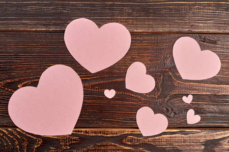 Paper hearts on brown wooden background. Wooden textured background with pink heart shaped paper decorations. Stok Fotoğraf