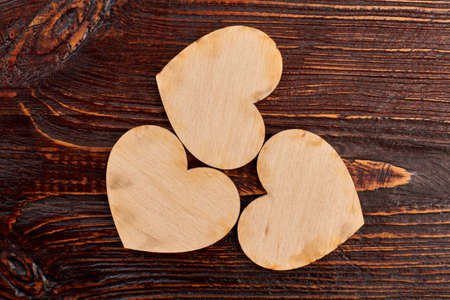 Three wooden hearts, top view. Vintage style wooden hearts on dark wooden background. Valentines holiday greeting card.
