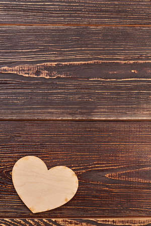 Plywood heart on brown wooden background. Blank wooden heart for decoupage and copy space.