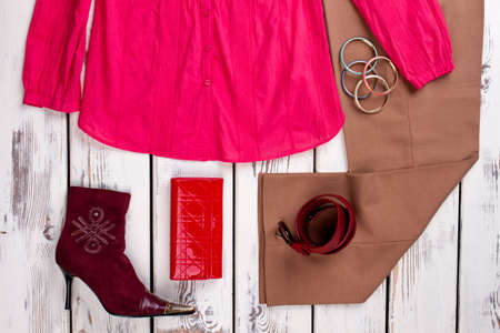Set of womens clothes, flat lay. Arrangement of burgundy heel shoes, pink shirt, brown trousers, red womens wallet.
