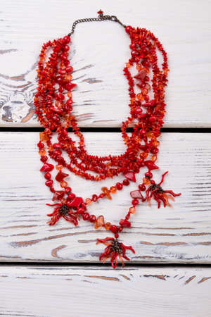 Red polished necklace. Jewelry with little red stones, beige wooden desks surface background. Imagens