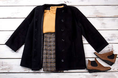 Winter outfit with black cashmere coat. Pair of brown suede women boots.