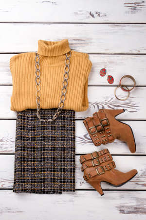 Winter female outfit with accessories. Boots with clasps, braceletes and earrings. Imagens