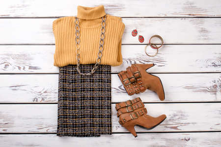 Women winter wear with boots and accessories. White wooden desks surface background. Top view. Imagens