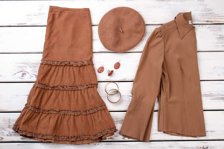 Folded women cardigan and dress skirt. Beret, earrings and braceletes. White wooden desks surface background.