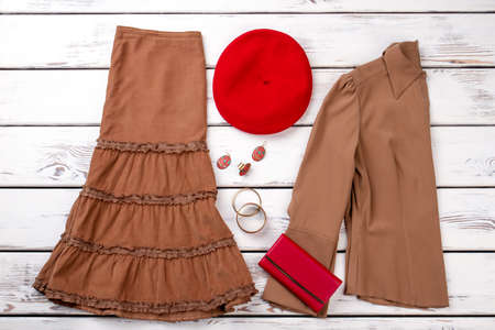 Brown clothes, red wallet and berete hat. White wooden desks surface background.