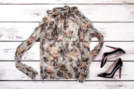 Flat lay cotton colourful ruffle blouse. Black shiny heel shoes.