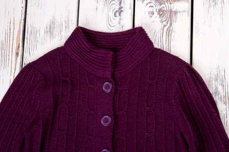 Collar of purple woolen sweater. Pullover with buttons, front view. Bright wooden desk background.