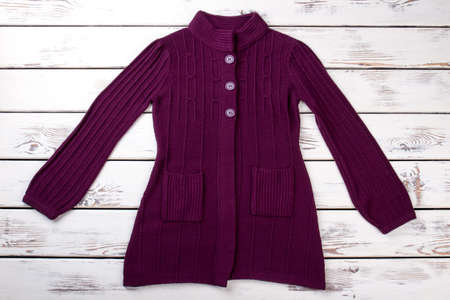 Long purple pullover coat. Burgundy patterned woolen sweater. Bright wooden desk background. Stockfoto