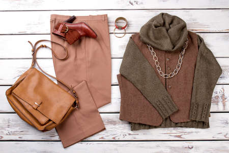 Womens fashion, casual outfits with accessories, flat lay, top view. Yellow leather purse, brown trousers, warm sweater.
