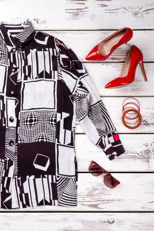 Abstract blouse print and red shoes. Summer sunglasses. White wooden background.