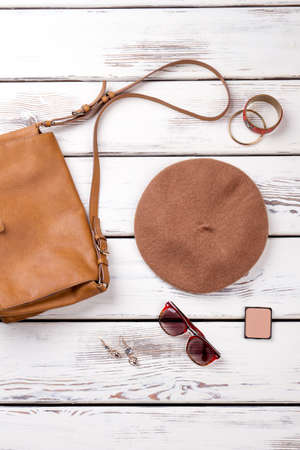 Female summer accessories. Top view spectacles, hat and cosmetic powder. Bright wooden background.