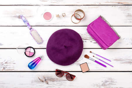 Purple womens accessories. Violet beret hat, purse, comb and brushes. Flat lay, top view. Imagens