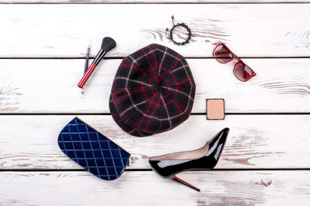 Woolen checkered hat and cosmetic makeup accessories, flat lay. Blue wallet, shiny high heel shoe, spectacles and brush. White wooden background.