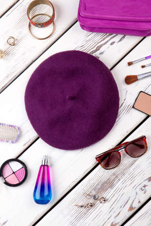Collection of cosmetic accessories. Purple violet beret hat, spectacles and perfume. Imagens