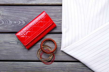 Close up red shiny wallet and braceletes. Striped clothes. Grey wooden surface background. Imagens
