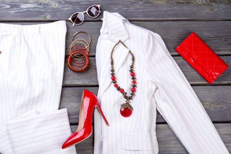 Top view womens clothes and accessories. Modish luxury suit and accessories. Grey wooden surface background. Imagens
