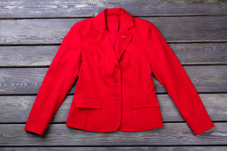 Flat lay red jacket. Womens suit, grey wooden surface background.